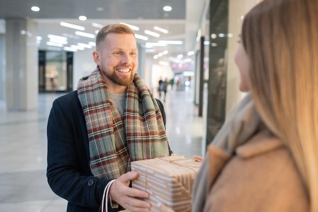 陽気な若い男がクリスマスに彼の妻を祝って、プレゼントモール内で彼女のギフトボックスを渡す
