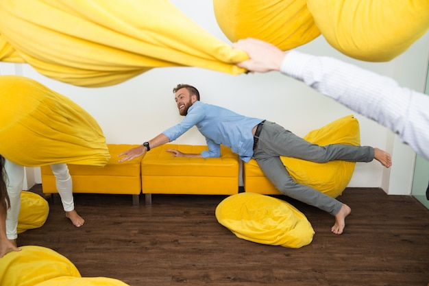 Cheerful young man on couch among flying beanbags