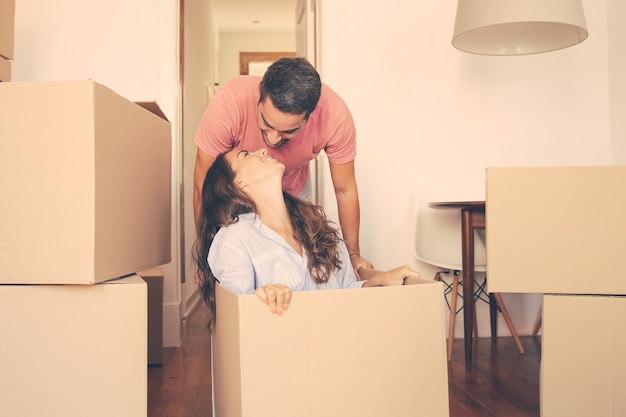 陽気な若い男が彼のガールフレンドを中に入れて箱を引きずり、彼女にキスします