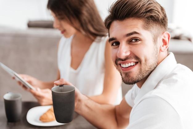 彼のガールフレンドがキッチンでタブレットを使用している間、陽気な若い男がコーヒーを飲む