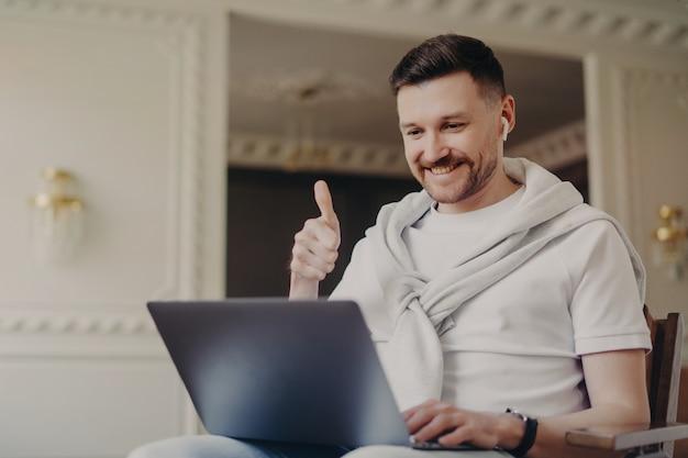 カジュアルな服装をした陽気な若い男性フリーランサーと、ノートパソコンでのビデオチャットで上司や同僚と話している間、自宅の明るい部屋に座っているようなワイヤレスイヤホンで指を上げている