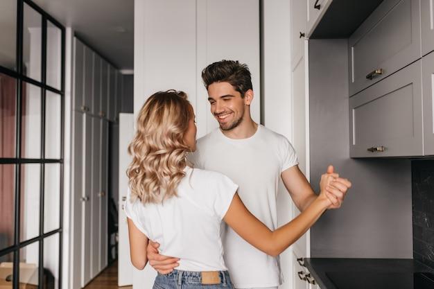 彼のガールフレンドを優しく抱きしめる陽気な若い男。週末の朝にキッチンで踊るカップル。