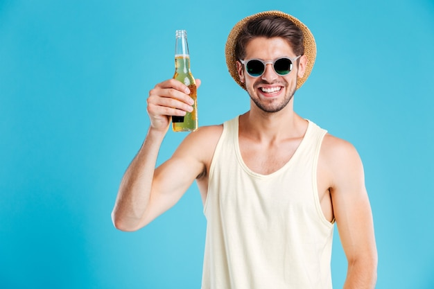 Cheerful young man in hat and sunglasses standing and drinking beer over blue wall