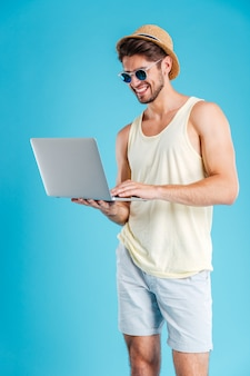 Cheerful young man in hat and sunglasses standing and holding laptop over blue wall