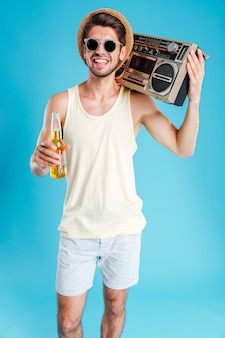 Cheerful young man in hat and sunglasses with boombox walking and drinking beer over blue wall