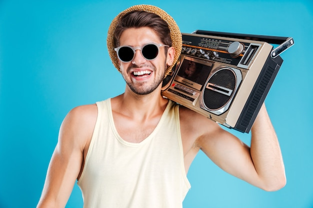 Cheerful young man in hat and sunglasses with boombox