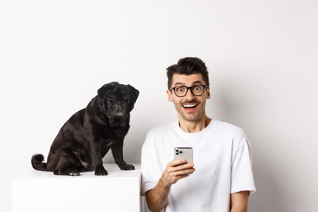 Cheerful young man hipster staring at camera, sitting with cute black pug dog and using mobile phone, standing over white background.