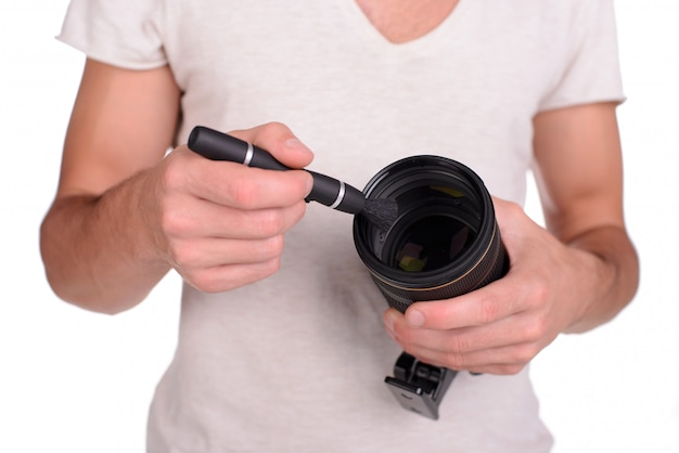 Cheerful young man holding camera and brush.