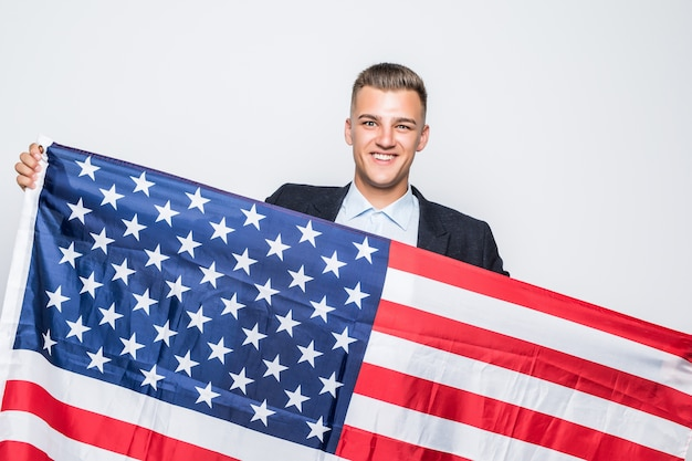 Cheerful young man holding flag of united states grey