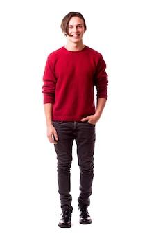 주머니에 손을 잡고 흰 벽에 서있는 동안 정면을보고 쾌활한 젊은 남자