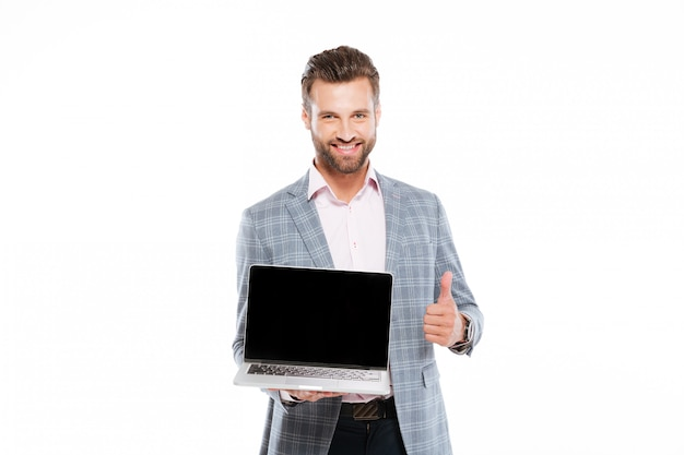 Cheerful young man holding laptop showing thumbs up.