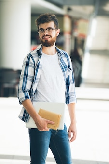 Cheerful young man holding notebook and laptop and looking sideways