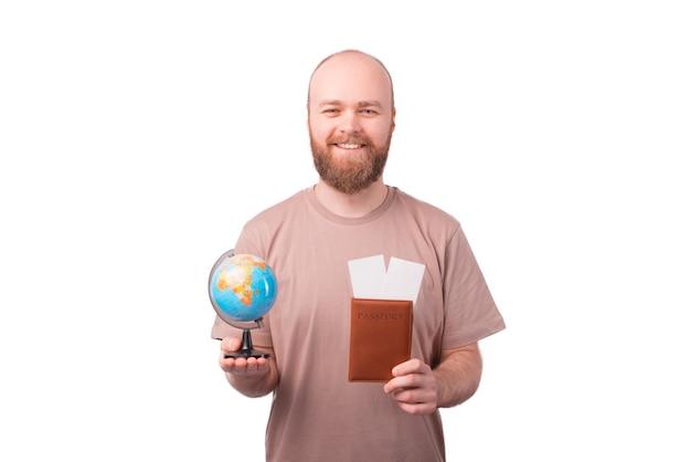비행기 티켓으로 여권과 지구본을 들고 쾌활한 젊은 남자가 세계를 여행 할 수 있습니다