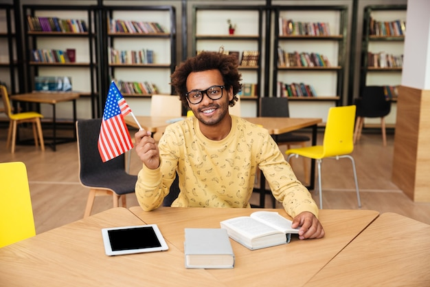 Cheerful young man holding united states flag sitting in library