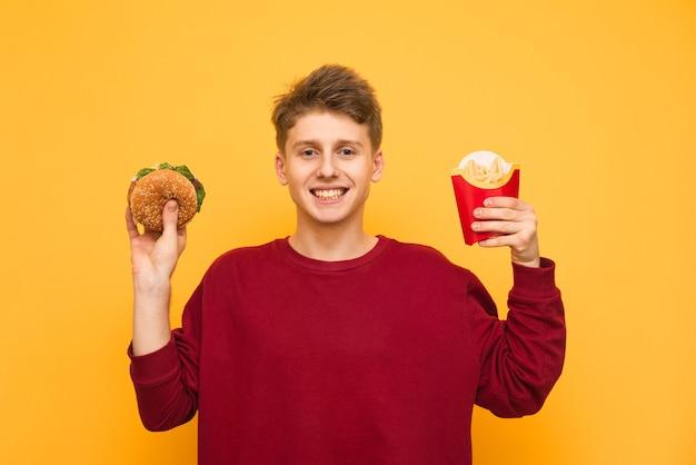 陽気な若い男が彼の手でフライドポテトとハンバーガーを保持しています。