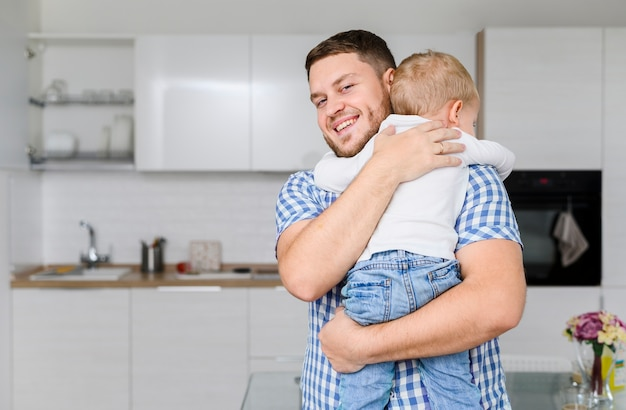 Cheerful young man hugging a child