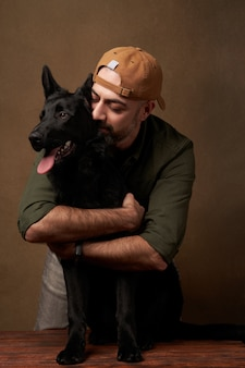 室内のポートレート、彼の犬を抱いて陽気な若い男