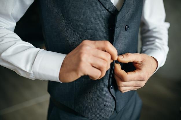 灰色のスーツを着た陽気な青年がジャケットに触れる