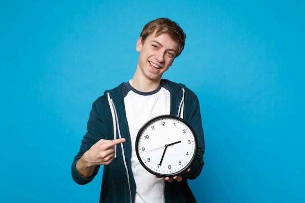 Веселый молодой человек в холдинге повседневной одежды, указывая указательным пальцем на круглые часы, изолированные на синей стене. время уходит. концепция образа жизни искренние эмоции людей.