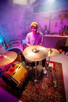 그의 차고에서 drumset 옆에 앉아 개별 리허설을하고 새로운 음악을 녹음 할 캐주얼웨어에 쾌활한 젊은 남자