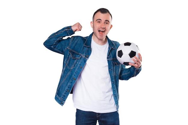 Веселый молодой человек в синих джинсах празднует и держит в руках футбольный мяч