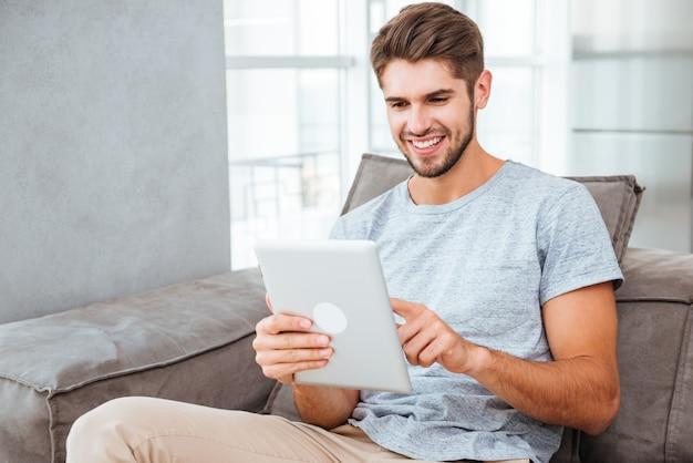 Веселый молодой человек в серой футболке сидит на диване у себя дома во время чата с помощью планшета.