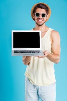 Веселый молодой человек в шляпе и солнцезащитных очках стоит и держит пустой экран ноутбука над синей стеной