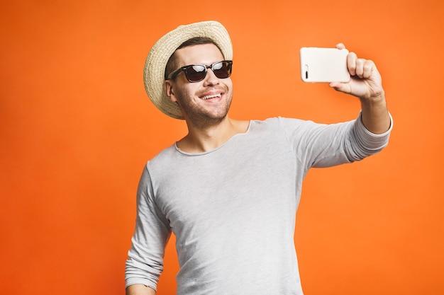 帽子とスマートフォンでselfieを取ってサングラスで明朗快活な青年