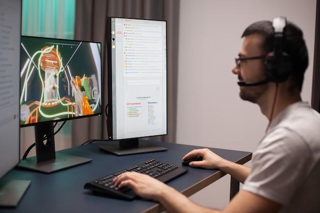 방에서 컴퓨터로 온라인 비디오 게임을 하는 쾌활한 젊은 남자.