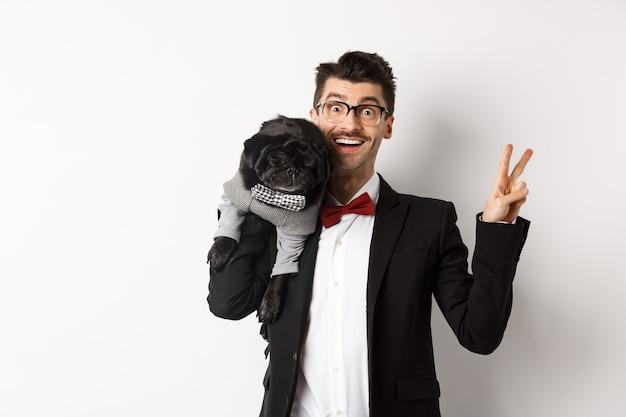 Веселый молодой человек в костюме и очках фотографирует с милой черной собакой мопса на плече, улыбается и показывает знак мира, позирует над белым.