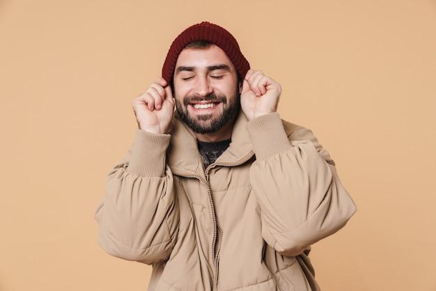 Веселый молодой человек в зимней куртке улыбается и надевает шляпу, изолированную над бежевой стеной