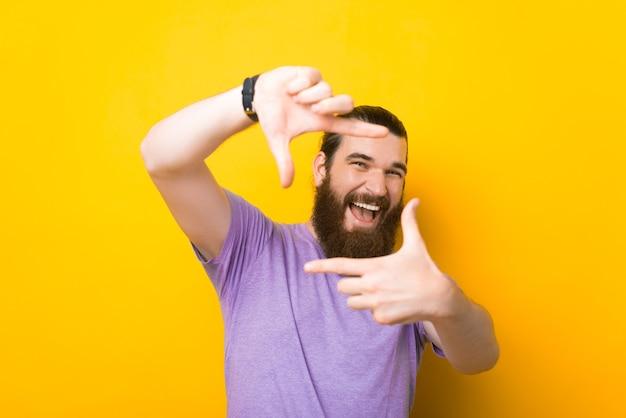陽気な若い男は、黄色の背景の上にフレームジェスチャーをしています。