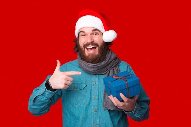 Веселый молодой человек указывает на синий подарок, который он держит.