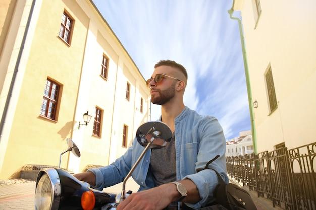 元気な青年が町のスクーターに乗っています。
