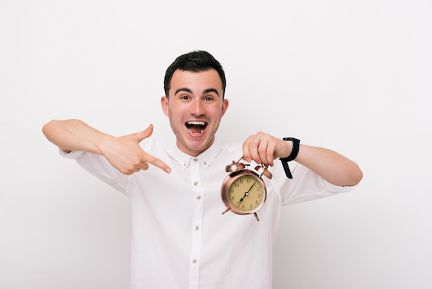 Cheerful young man is showing a clock in studio on a white background.