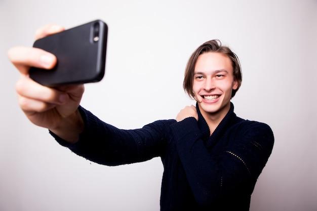쾌활한 젊은 남자가 검은 스마트 폰으로 셀카를 찍고 있으며, 그는 흰 벽에 회색 저지를 입고 있습니다.