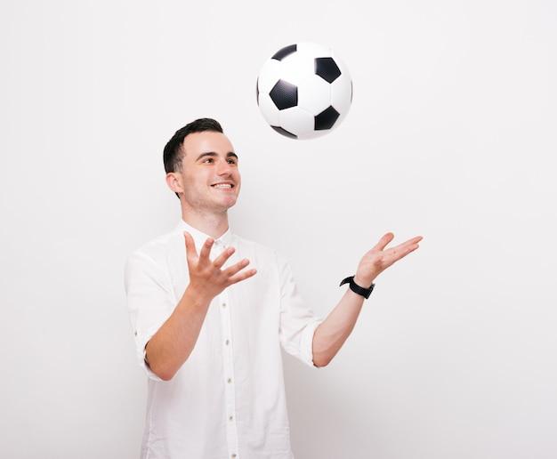 Веселый молодой человек бросает футбольный мяч