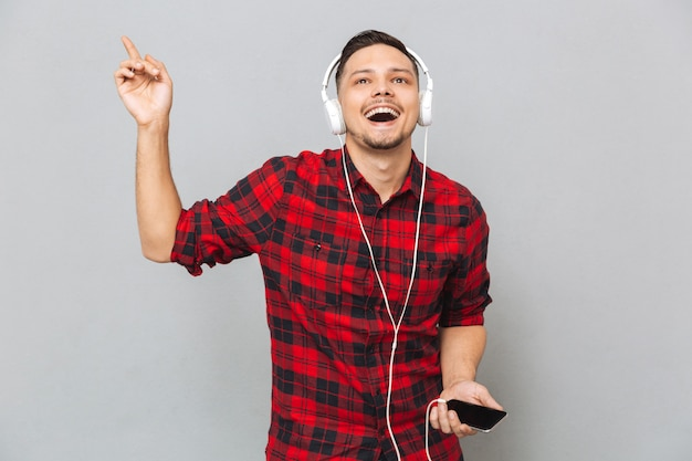 Cheerful young man listening music with headphones.