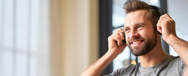 Веселый молодой человек слушает музыку через беспроводные наушники