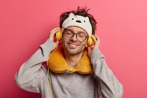 Веселый молодой человек слушает музыку в наушниках, приятно улыбается