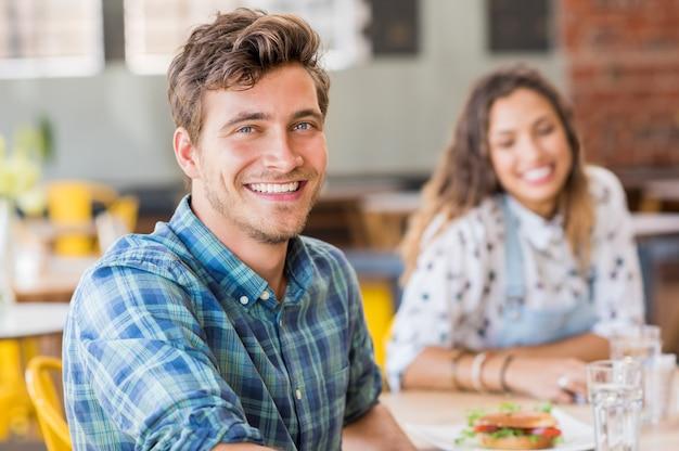 Веселый молодой человек смотрит вперед, пока ее друг улыбается в стене