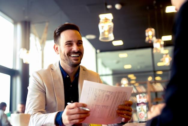 陽気な若い男はすべての紙の仕事をした後幸せそうに見える
