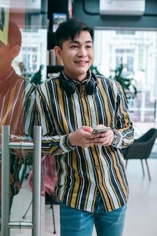 Веселый молодой человек у стеклянной двери стоит со смартфоном и смотрит в сторону