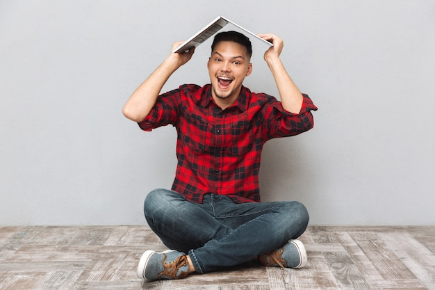 Cheerful young man in plaid sirt holding laptop over head