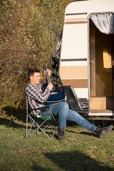 山の彼のレトロなキャンピングカーの前で彼のギターで遊んでいる陽気な若い男。山でリラックスした男。