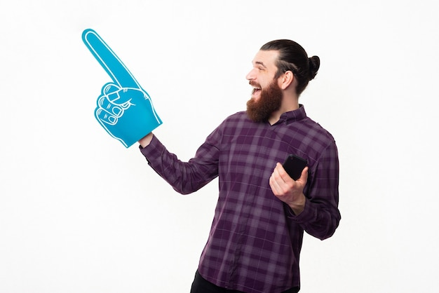 Cheerful young man pointing at copyspace with fan glove and holding smartphone