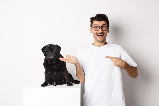 Веселый молодой человек указывая пальцем на свою собаку, показывая маленький милый черный мопс сидя, на белом фоне.