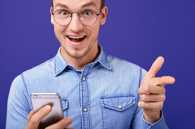 Cheerful young man pointing forward with hand joyfully