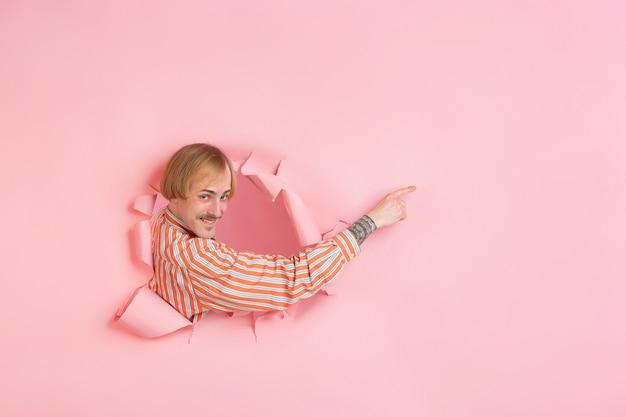 陽気な若い男は、感情的で表現力豊かな引き裂かれた珊瑚紙の穴の壁でポーズをとる