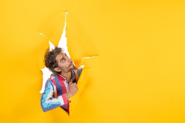 陽気な若い男は、感情的で表現力豊かな黄色の紙の穴の背景を引き裂いてポーズをとる